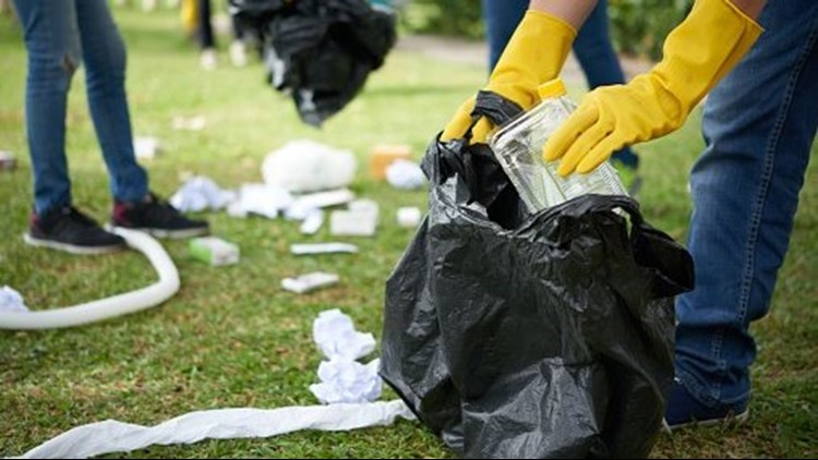 Family Picking Up Trash In Spring Park Wearing Protective Gloves Focus On Boy Hand With