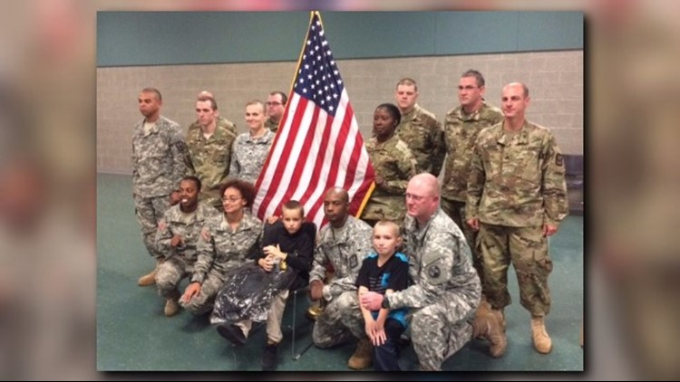 Xzayvier Buchard-Mease poses with SPC Larry Harris and several other members of the United States Army Reserves, upon conclusion of his honorary induction ceremony.